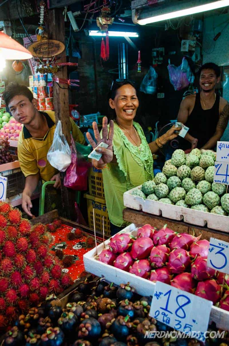 Smiling lady selling dragon fruit at Klong Toey Fresh Market in Bangkok