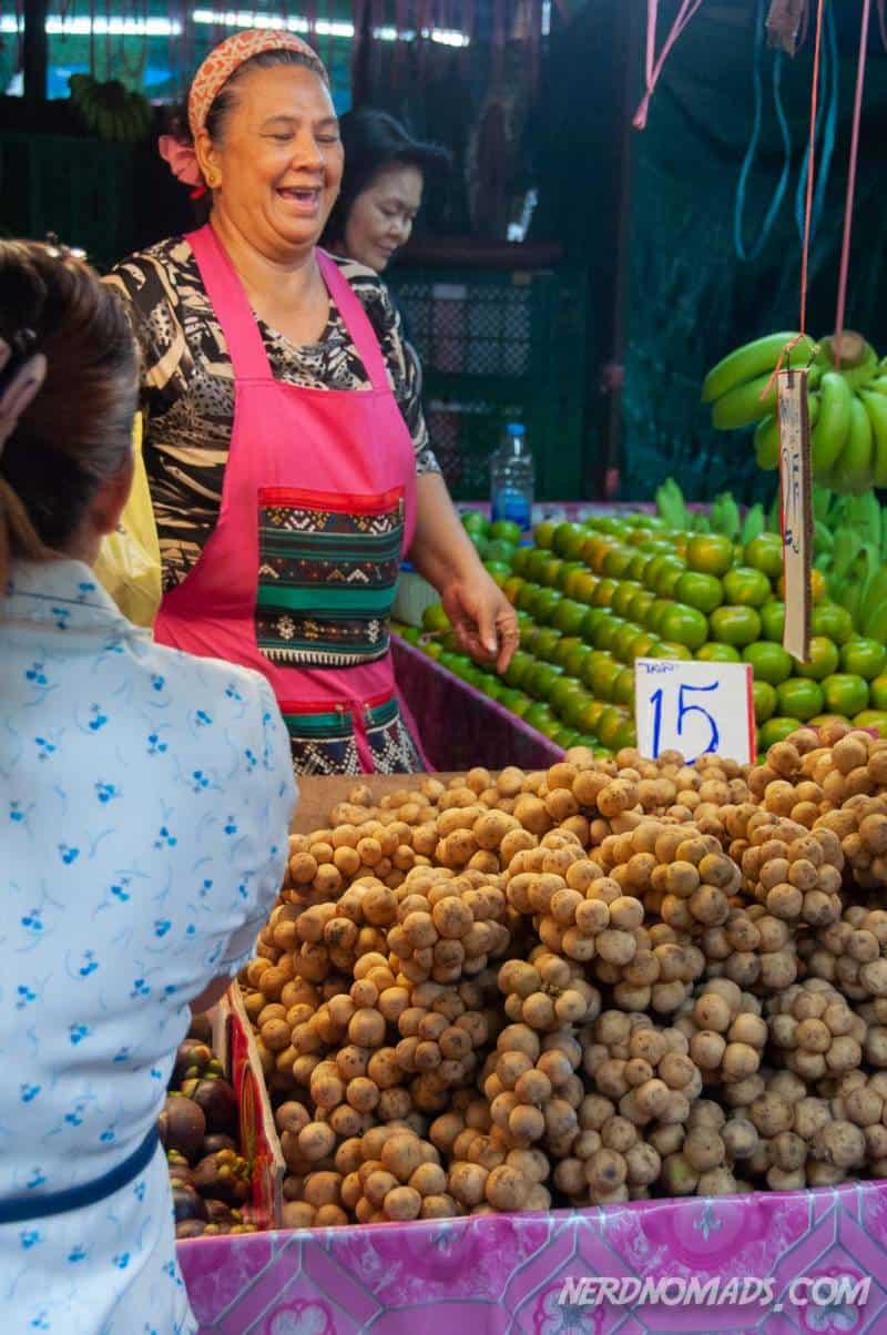 Woman selling longkan fruit at Klong Toei Market in Bangkok