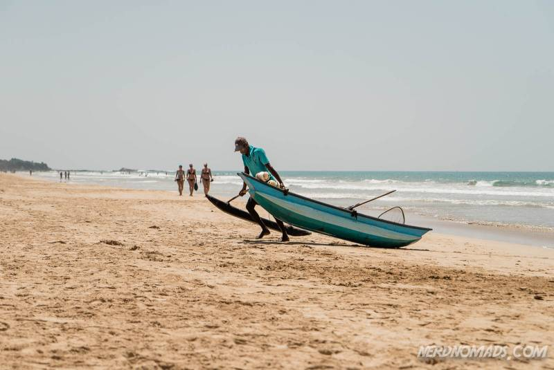 A local fisherman with his boat at Bentota Beach in Sri Lanka