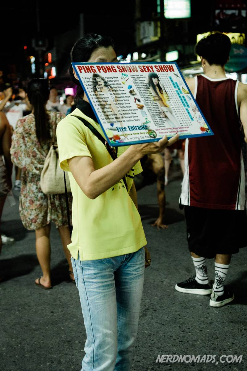 A woman with a poster promoting ping pong shows and sex shows in Patong, Phuket